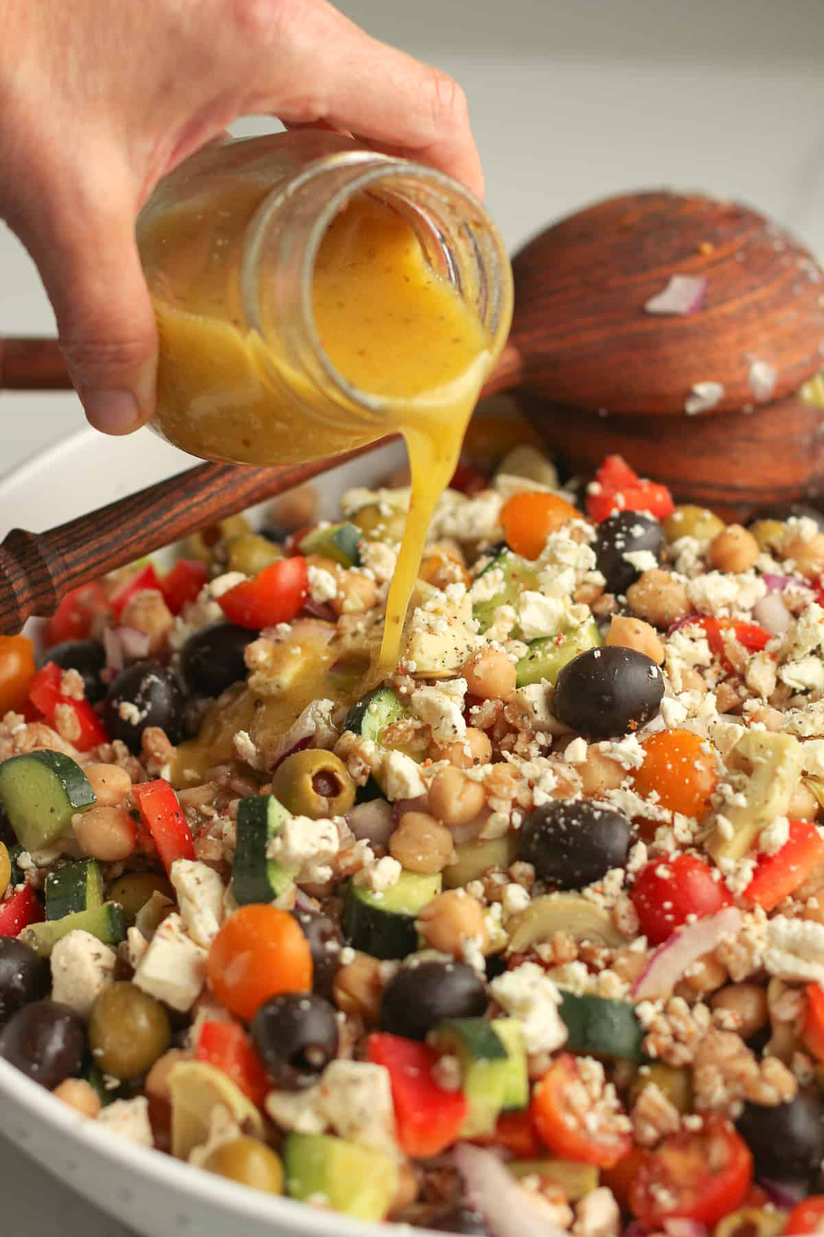 A hand drizzling some Greek Salad dressing on the salad.