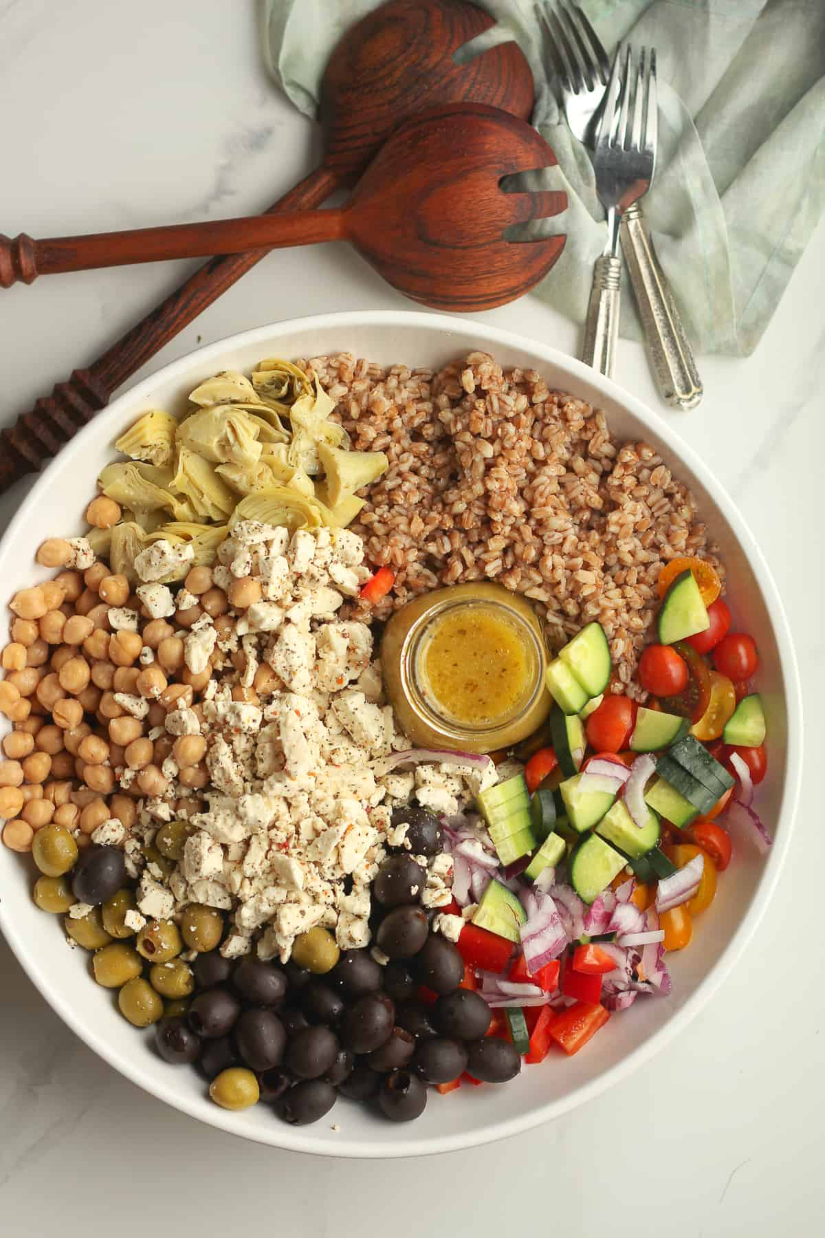 A large bowl of Greek farro salad separated by ingredient.