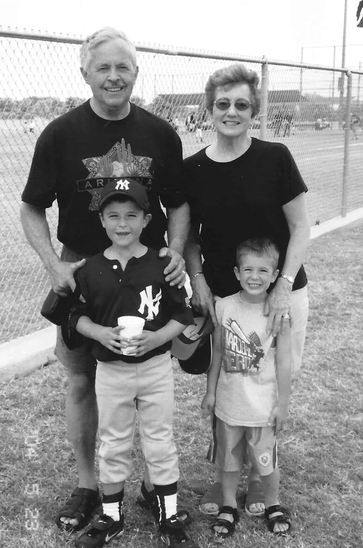 My parents at a baseball game, posed with our boys.