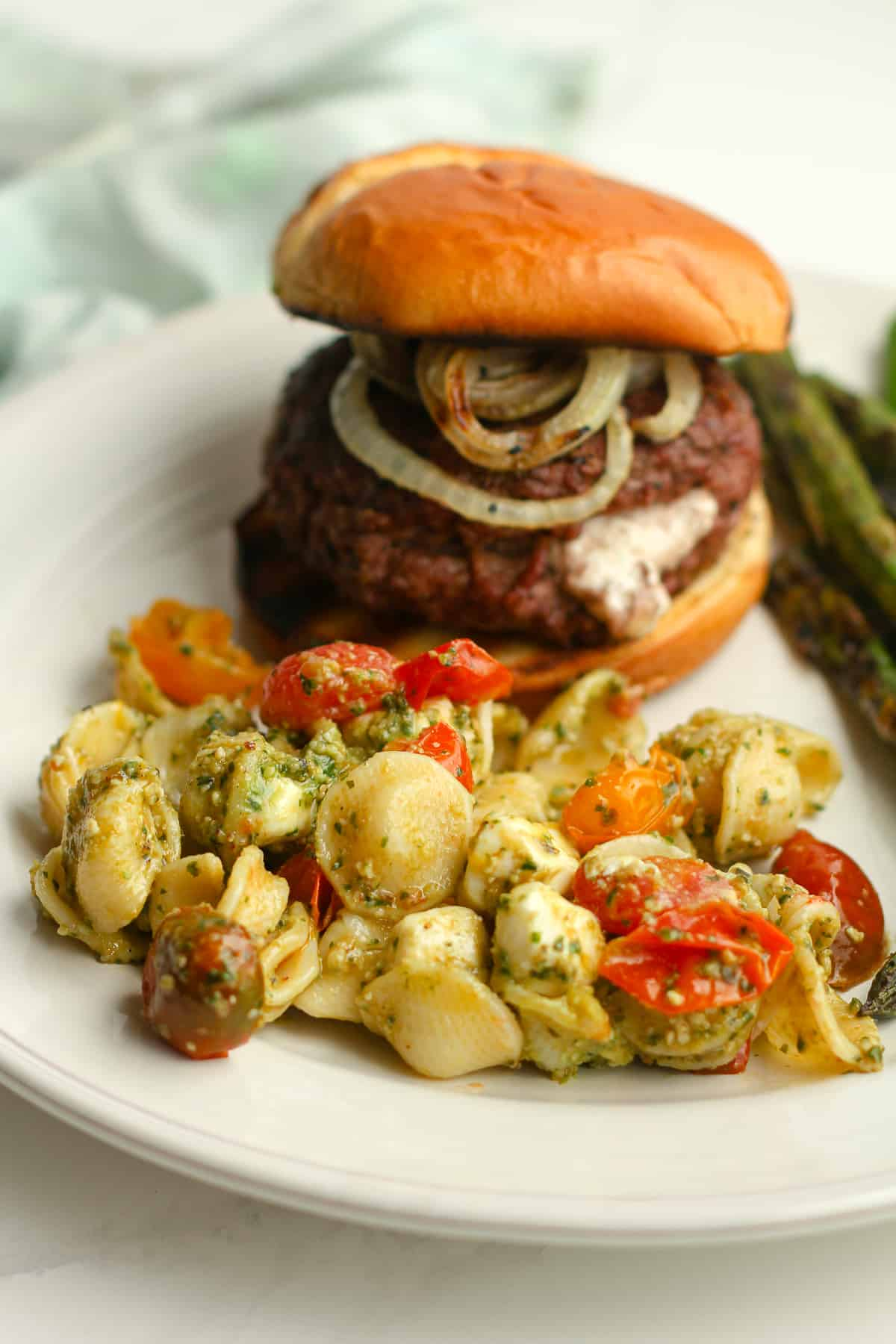 Side shot of a plate of pasta salad with a burger.