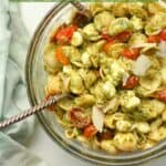 A bowl of pesto pasta salad with salad tongs.