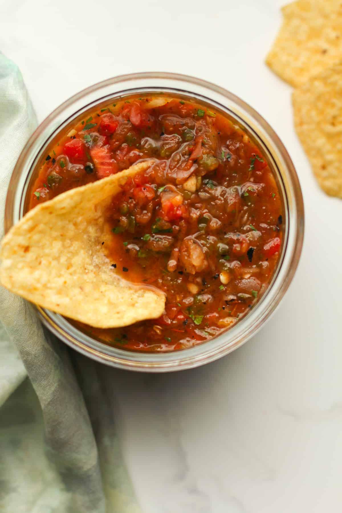 A jar of homemade salsa with a chip inside.