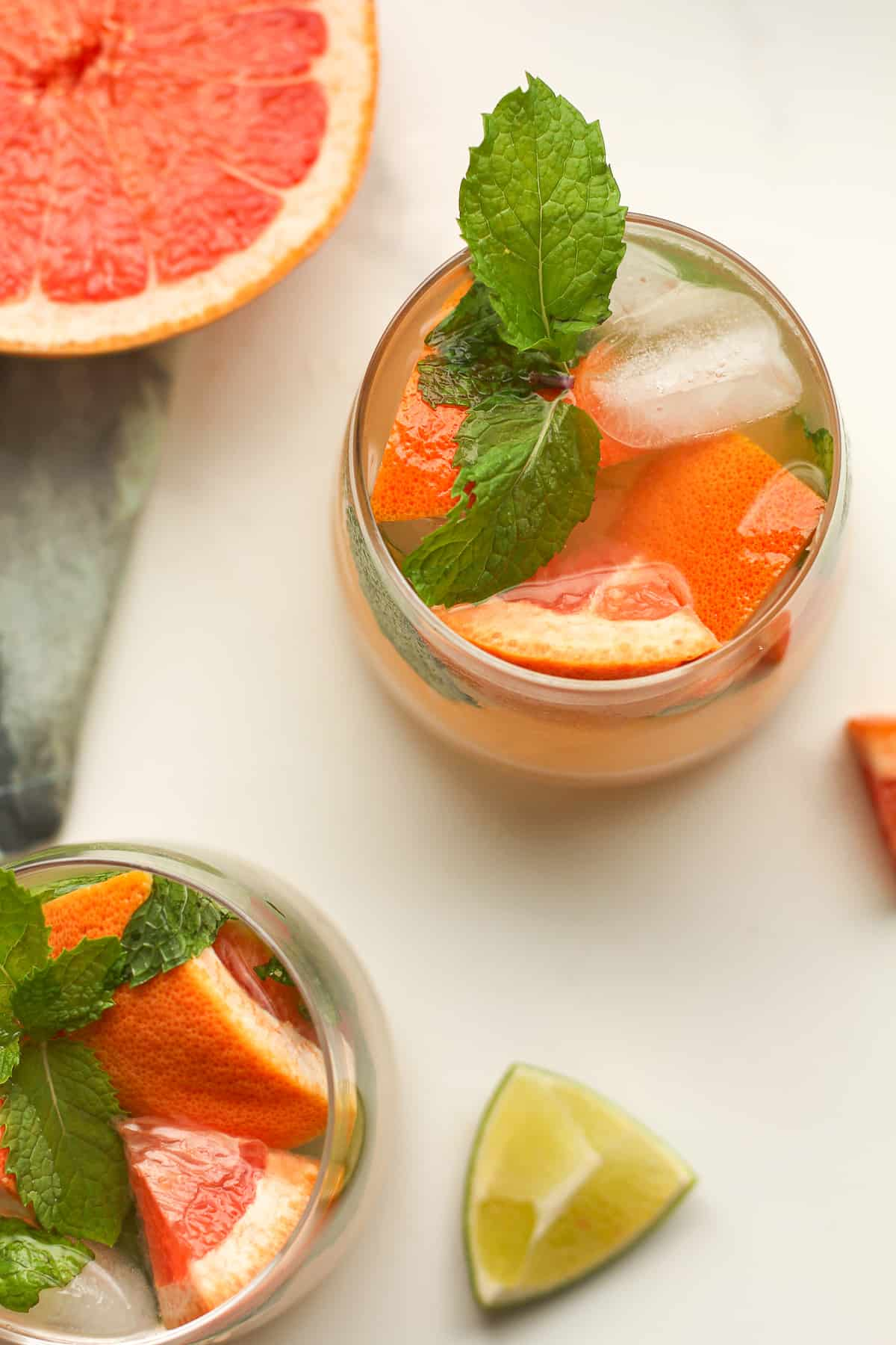Overhead shot of two glasses of grapefruit mojitos.