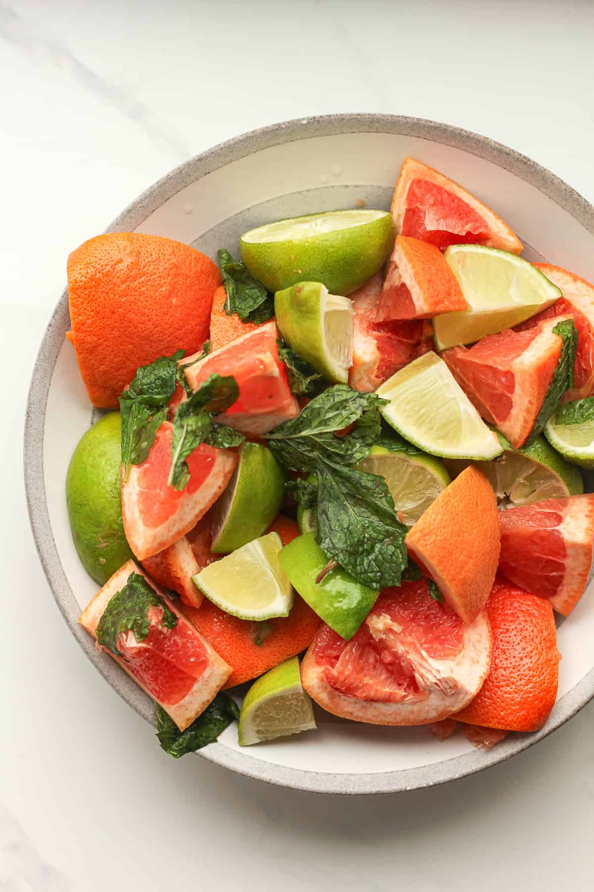 A bowl of chunks of grapefruit and limes.