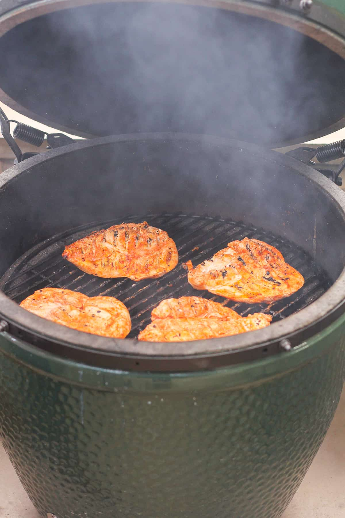 A big green egg with the chicken breasts.