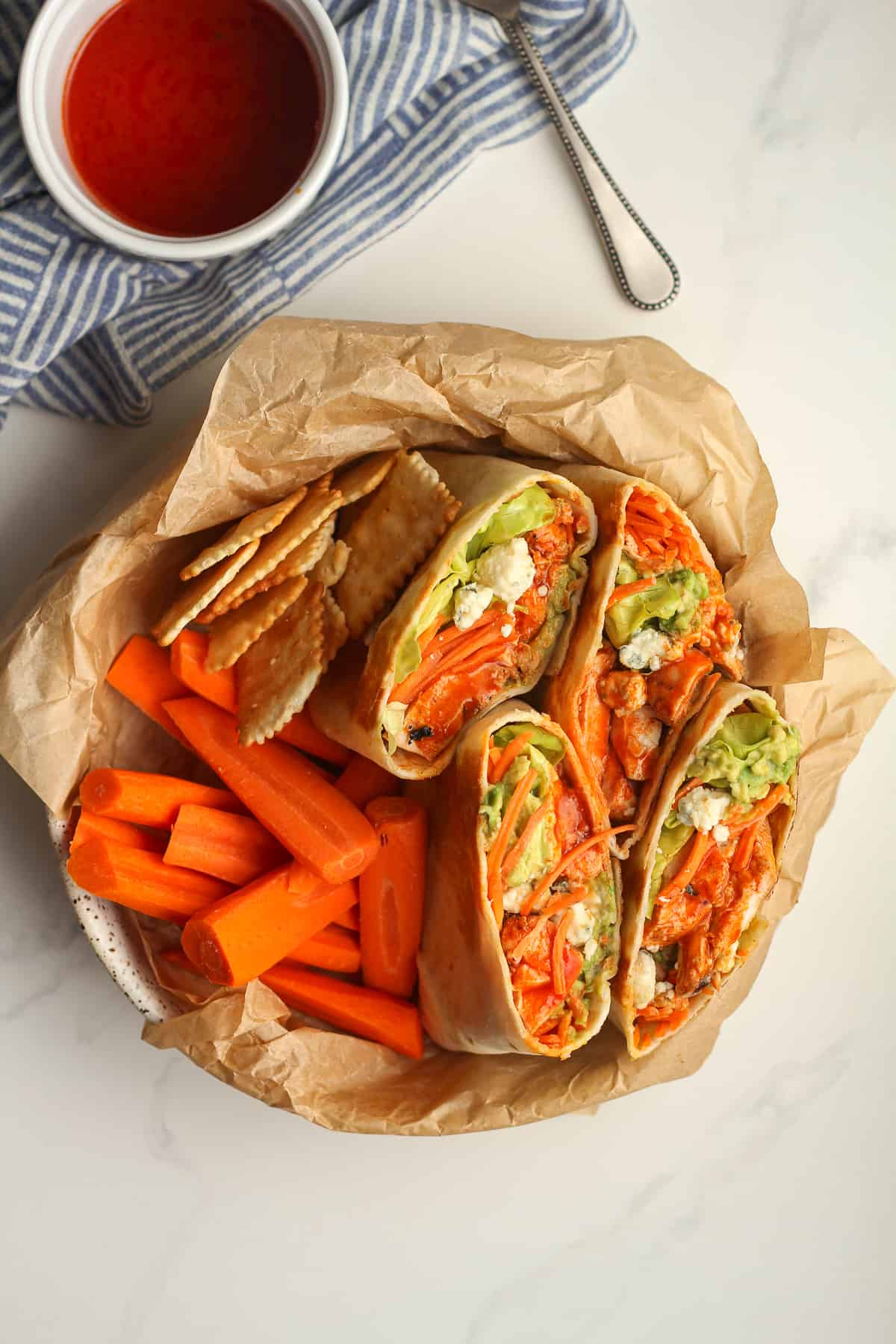 Overhead shot of a bowl of grilled buffalo chicken wraps, with a small bowl of sauce.