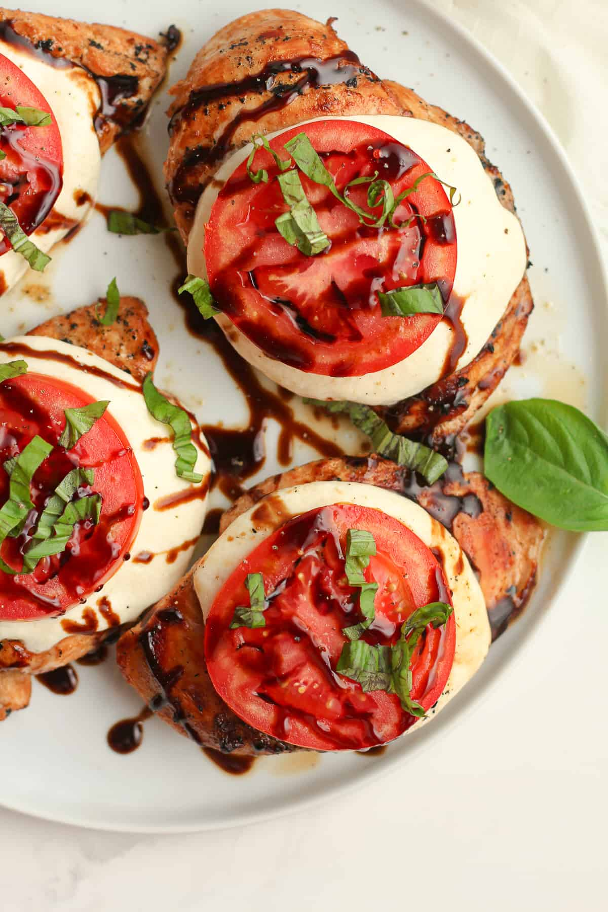 Closeup on some just grilled chicken with Caprese topping.