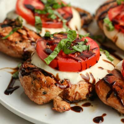 Side shot of a plate of grilled chicken Caprese.