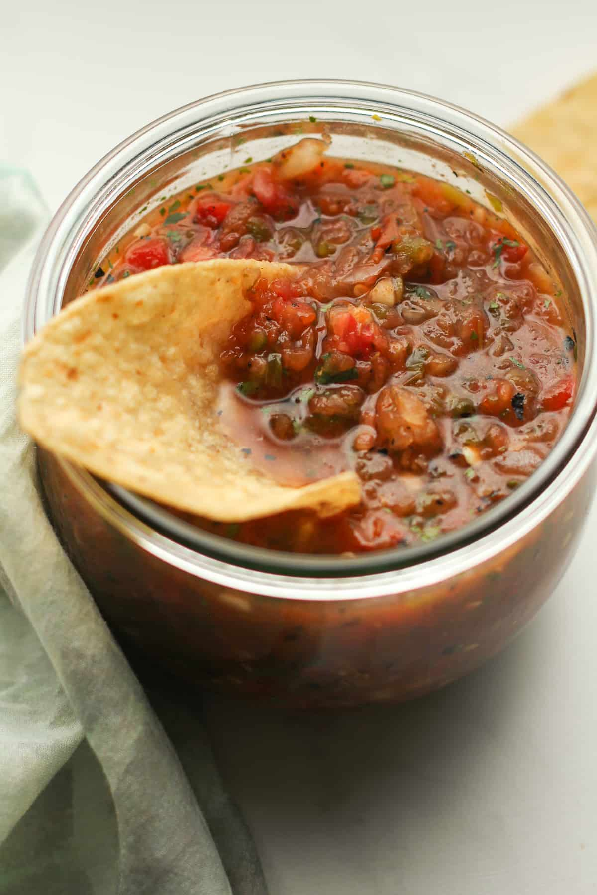 A closeup on a jar of grilled salsa with a chip.