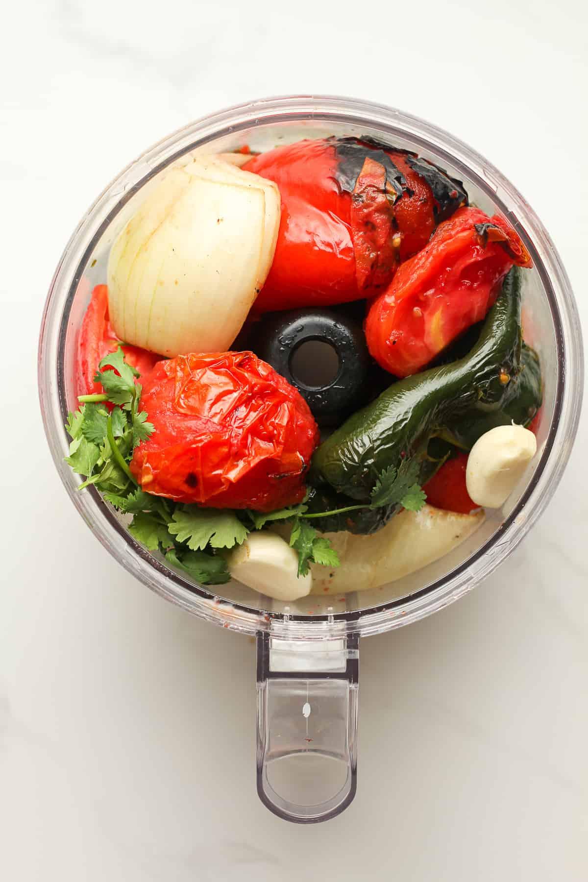 The food processor stuffed full of grilled veggies.