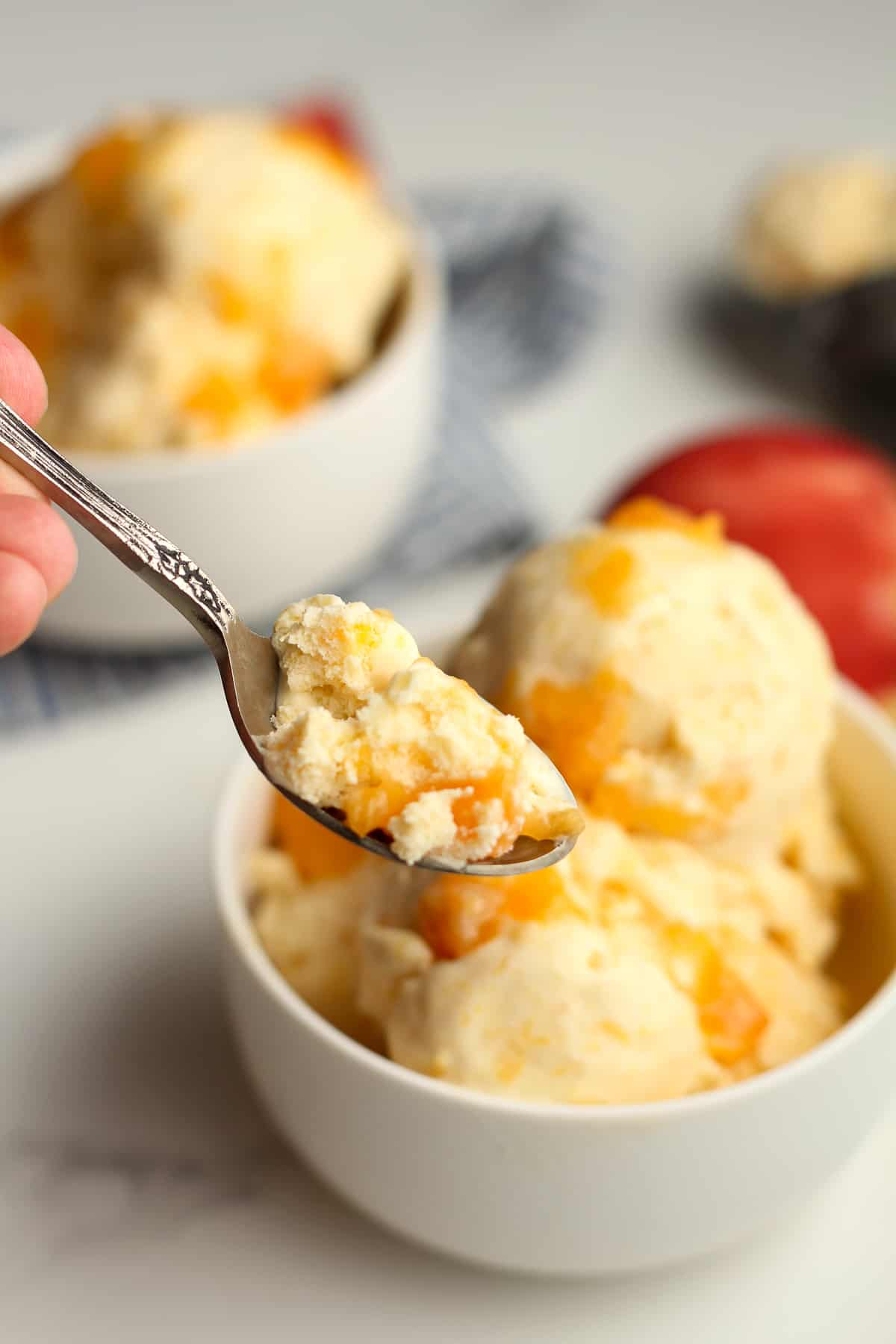 A spoonful of homemade peach ice cream, by a bowl.