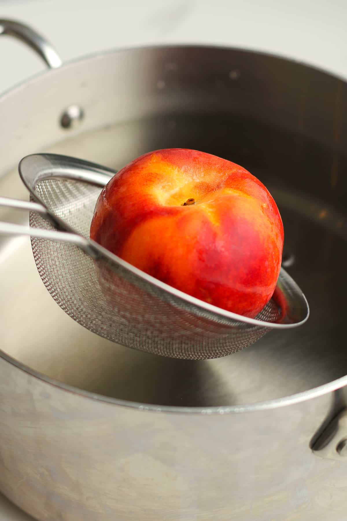 A pan of boiling water with a strainer pulling out a peach.