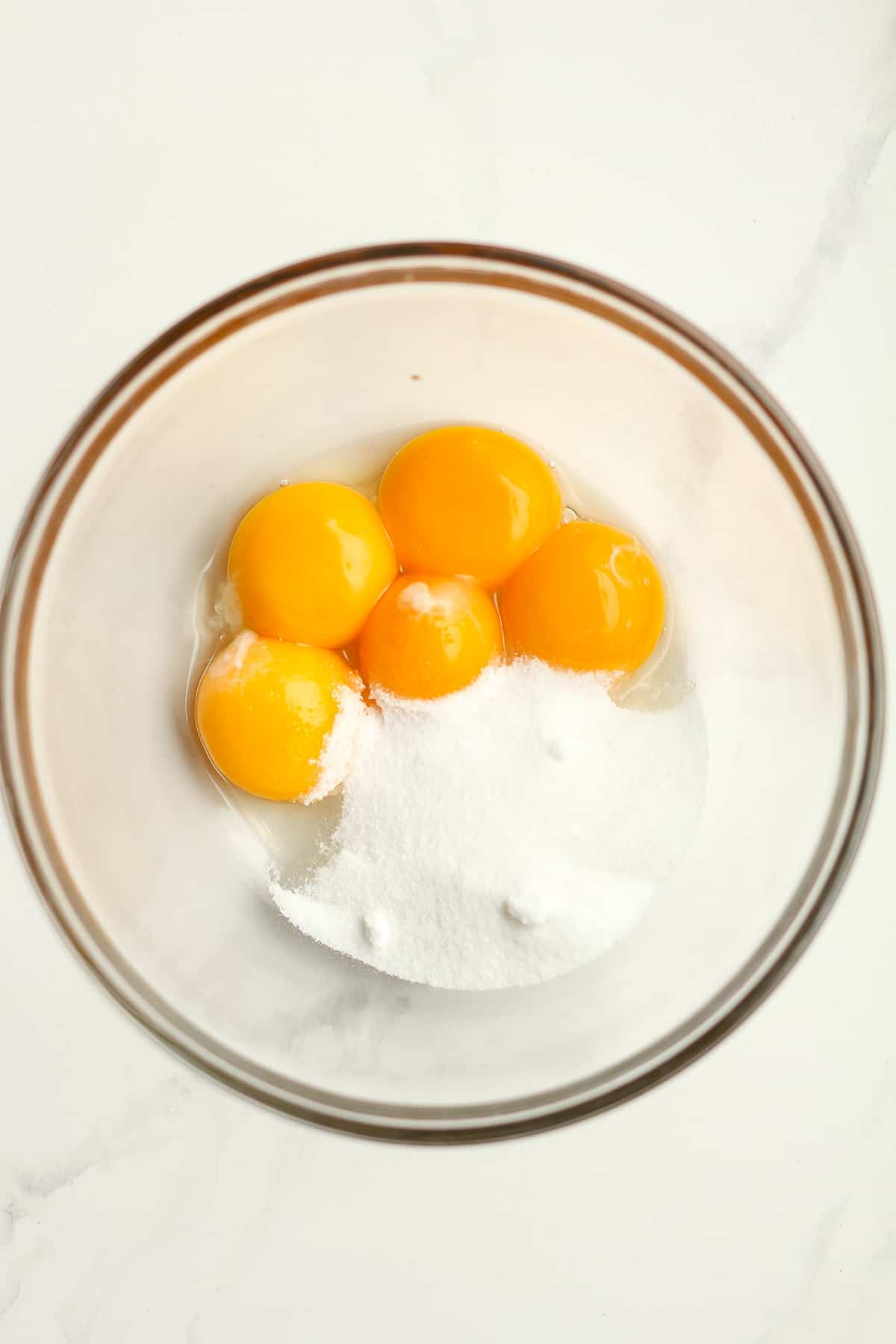 A bowl of 5 egg yolks with sugar.