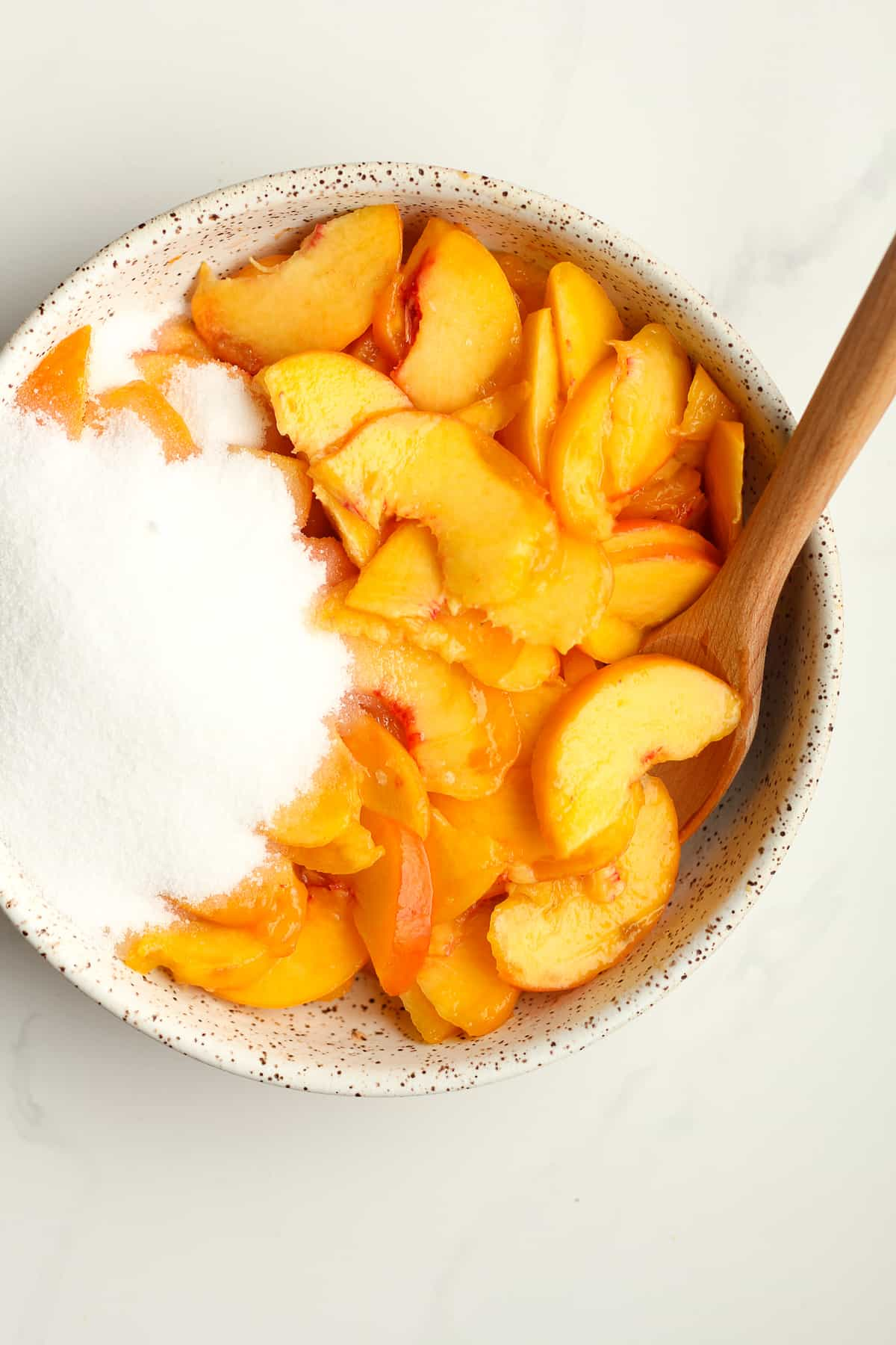 A bowl of sliced peaches with sugar.