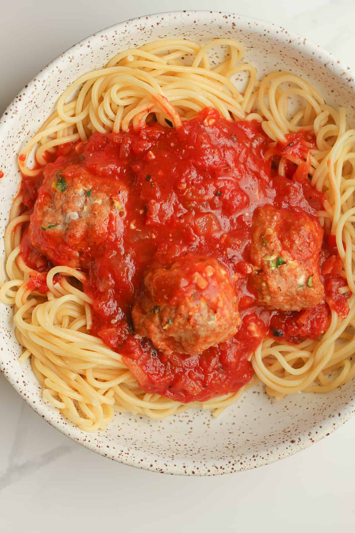 A bowl of the spaghetti with sauce and meatballs.
