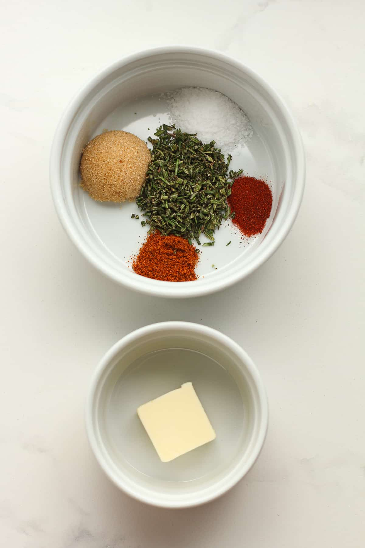 A bowl of the seasonings and a bowl of the butter.