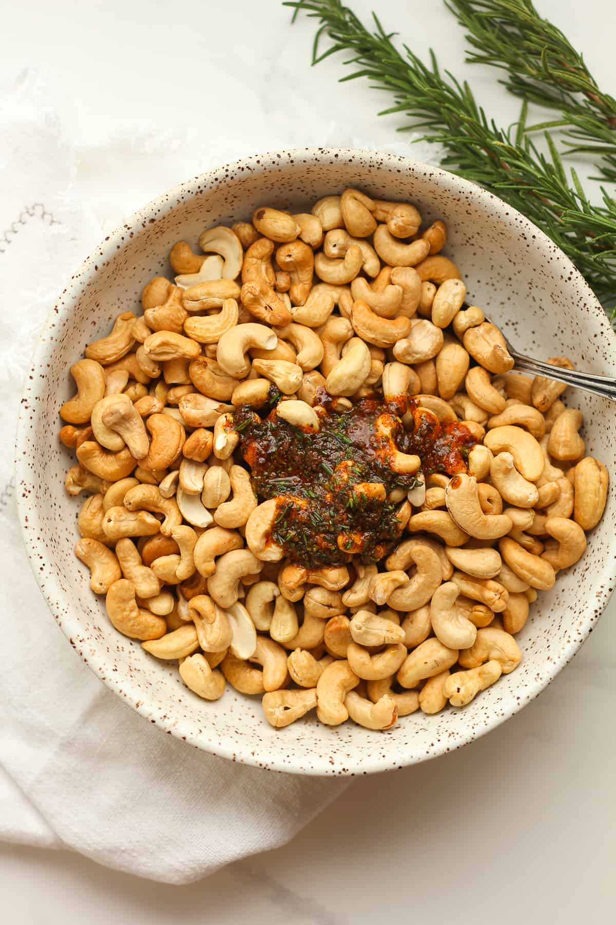 A bowl of the raw cashews with the seasoning mix.