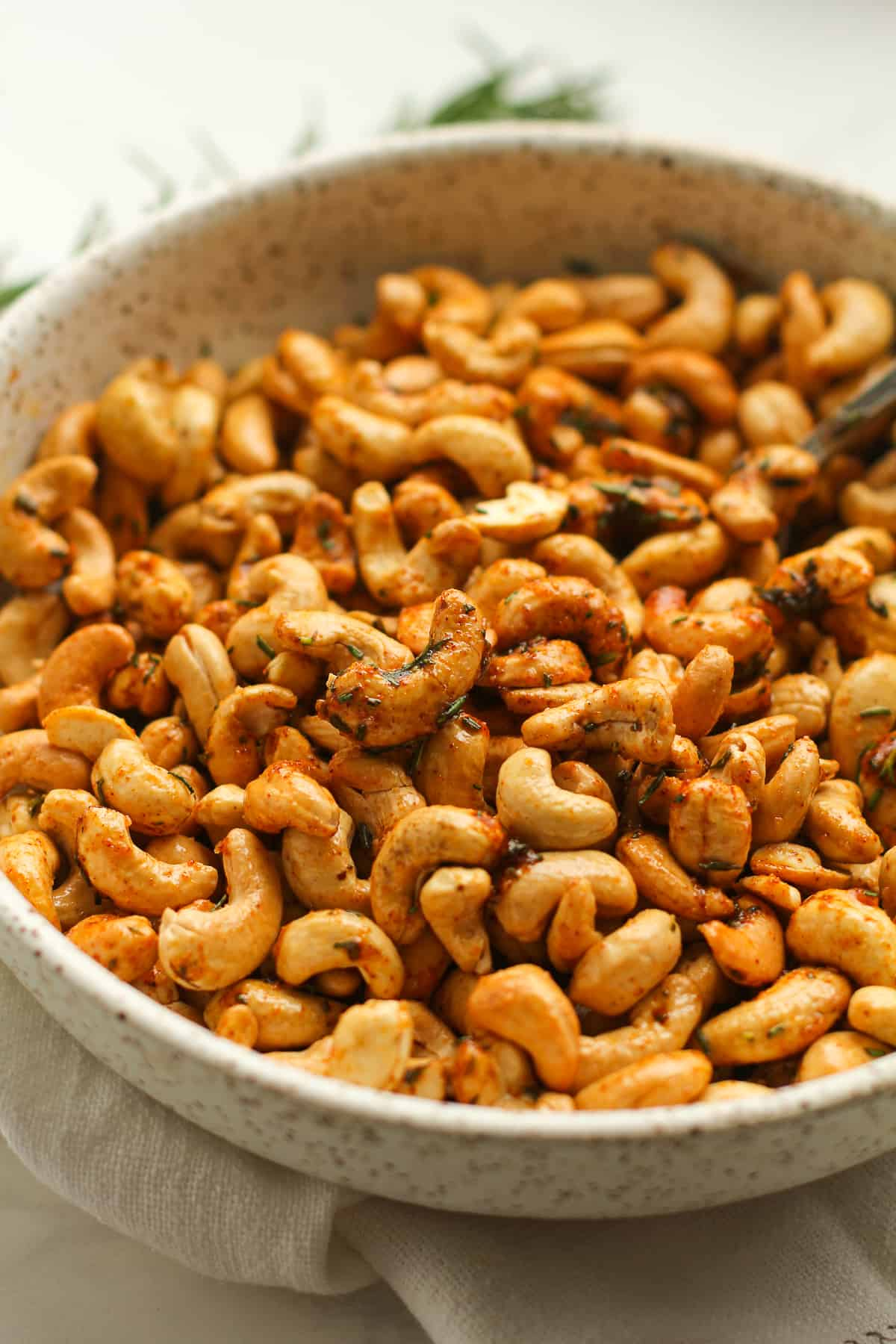 Side shot of a bowl of rosemary cashews.
