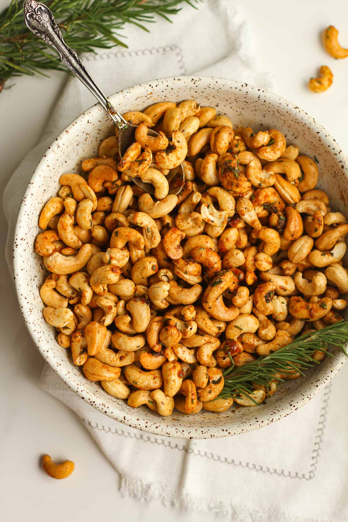 Overhead shot of a bowl of roasted rosemary cashews with a spoon.