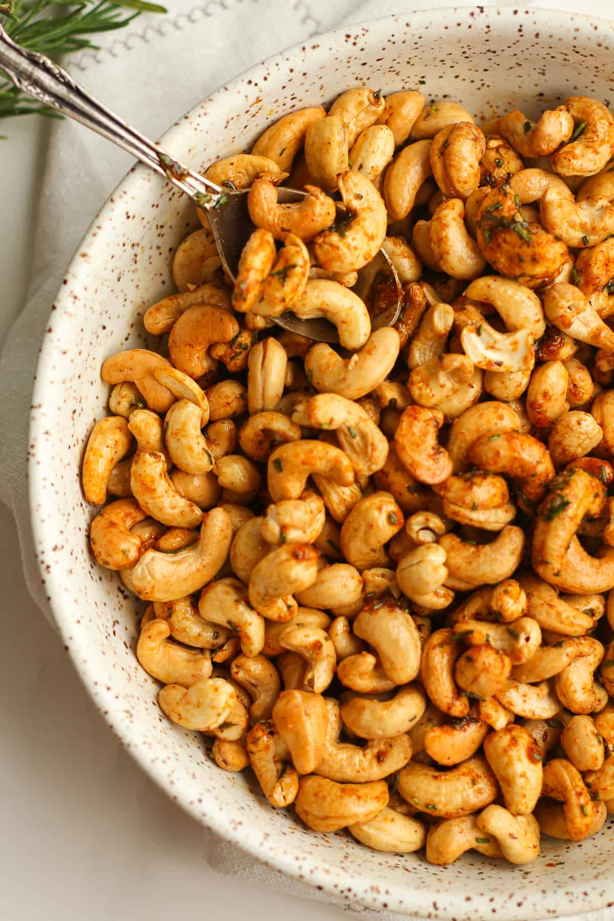 A closeup on a bowl of rosemary cashews.
