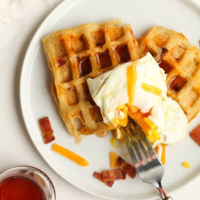 A plate of waffles with an egg on top.