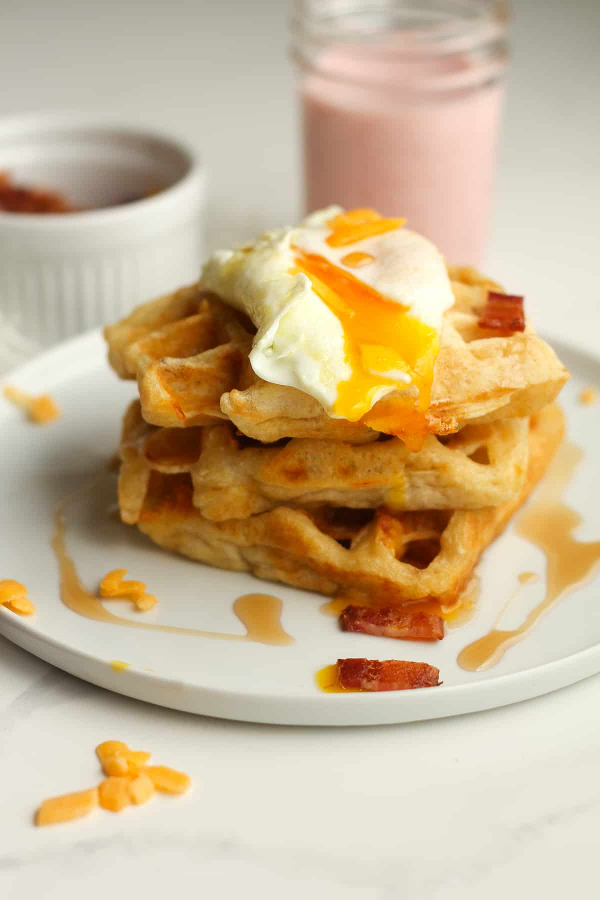A stack of three waffles with a drippy egg on top.