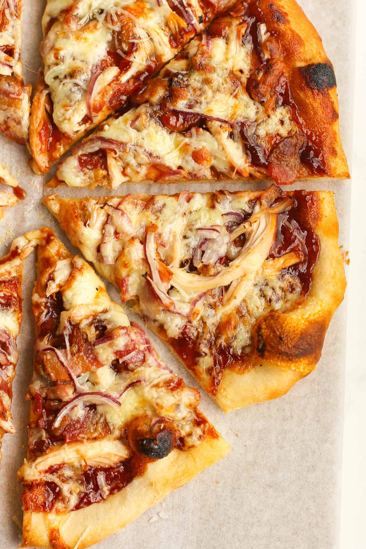 Closeup on three slices of chicken bacon pizza.