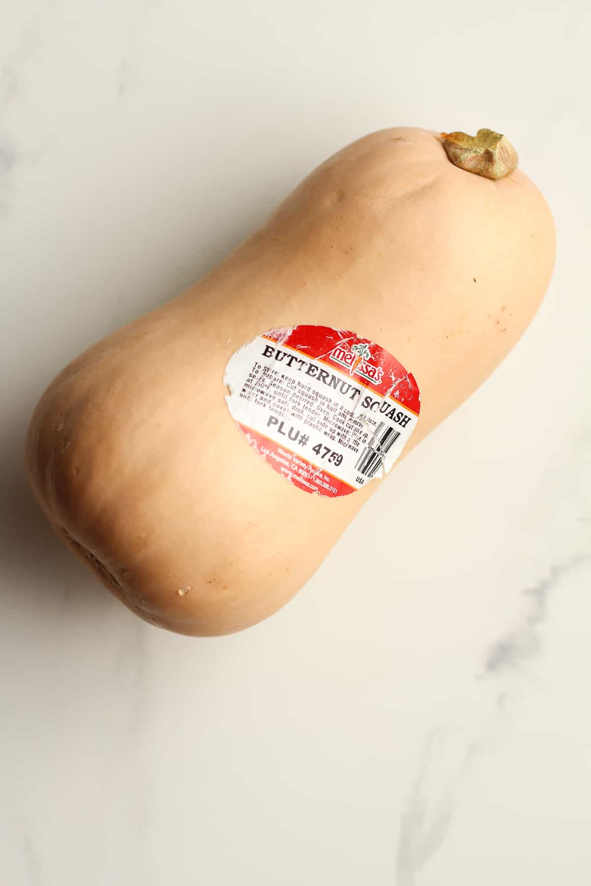 A butternut squash with the Melissa's tag.