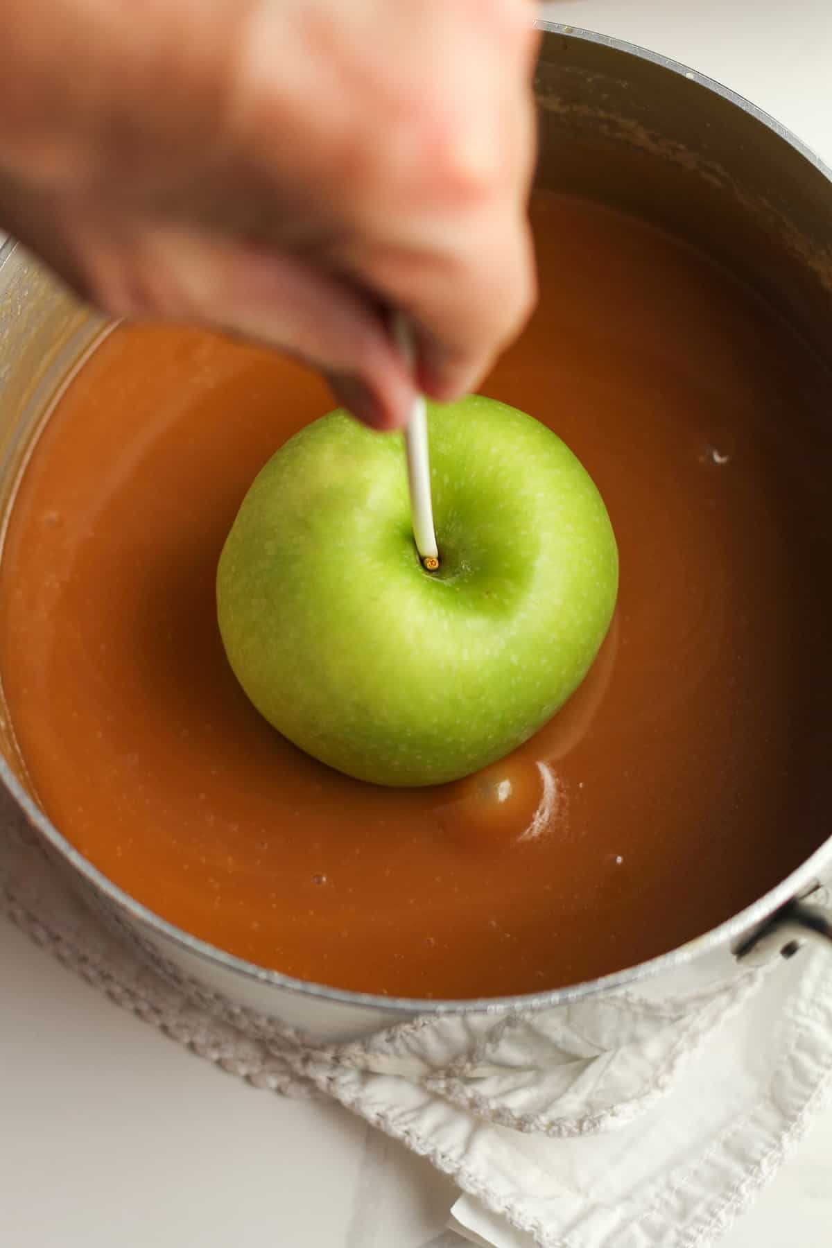 Overhead shot of the apple dipped in pan of caramel.