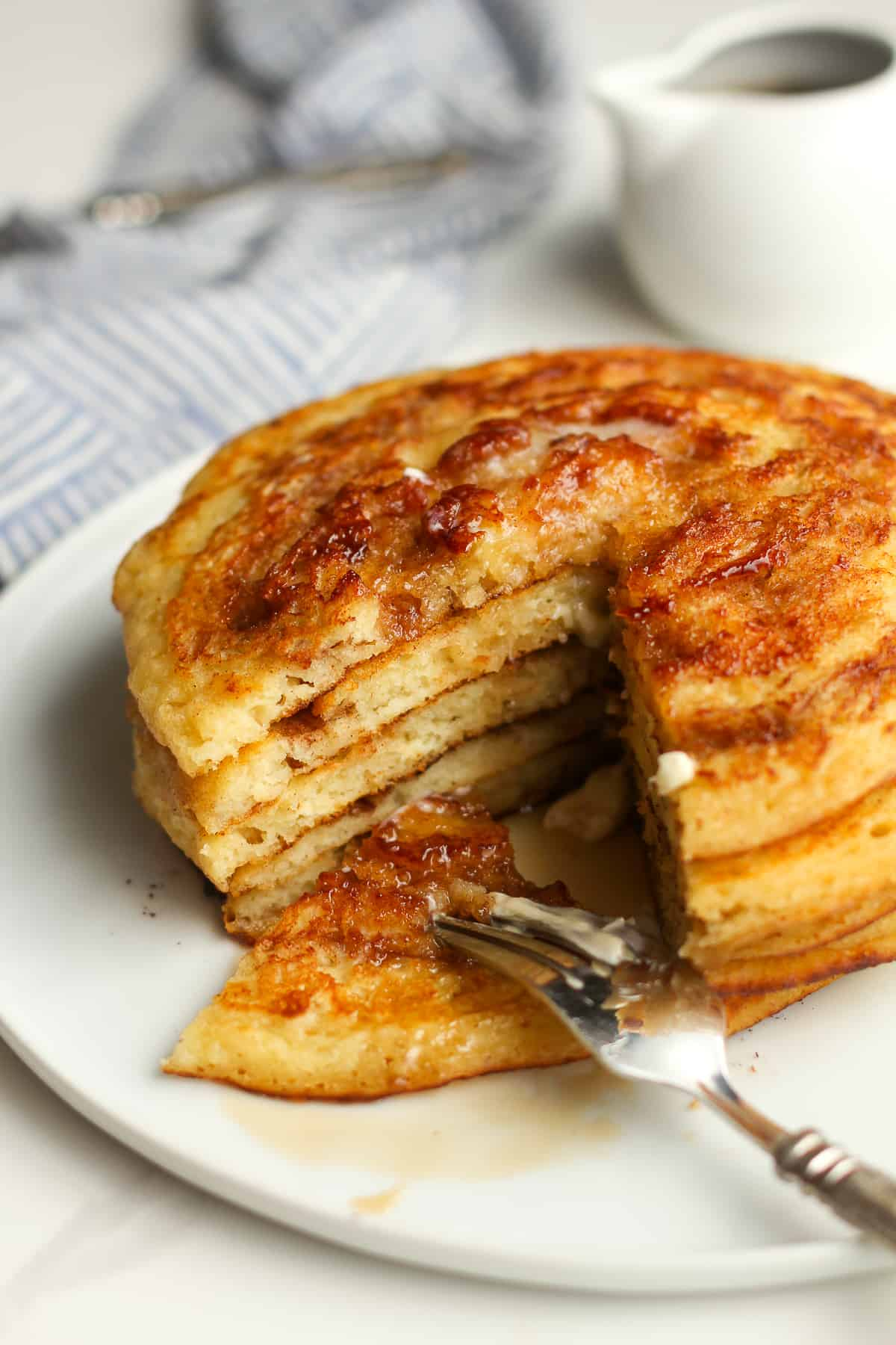 A plate of a stack of pancakes, with a section cut out.