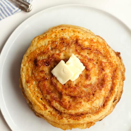 A stack of cinnamon swirl pancakes with butter.