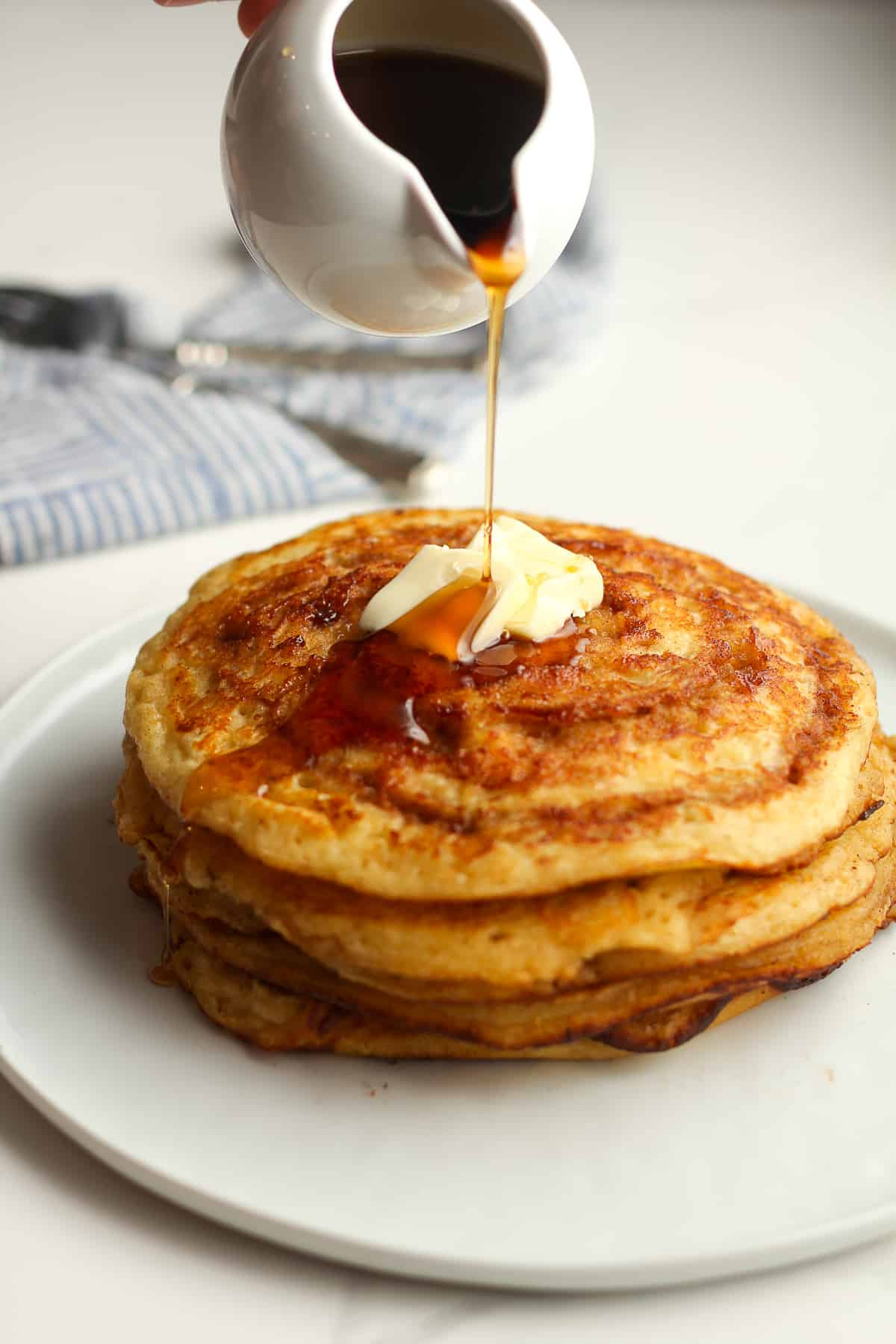 Some syrup drizzling on a stack of pancakes.
