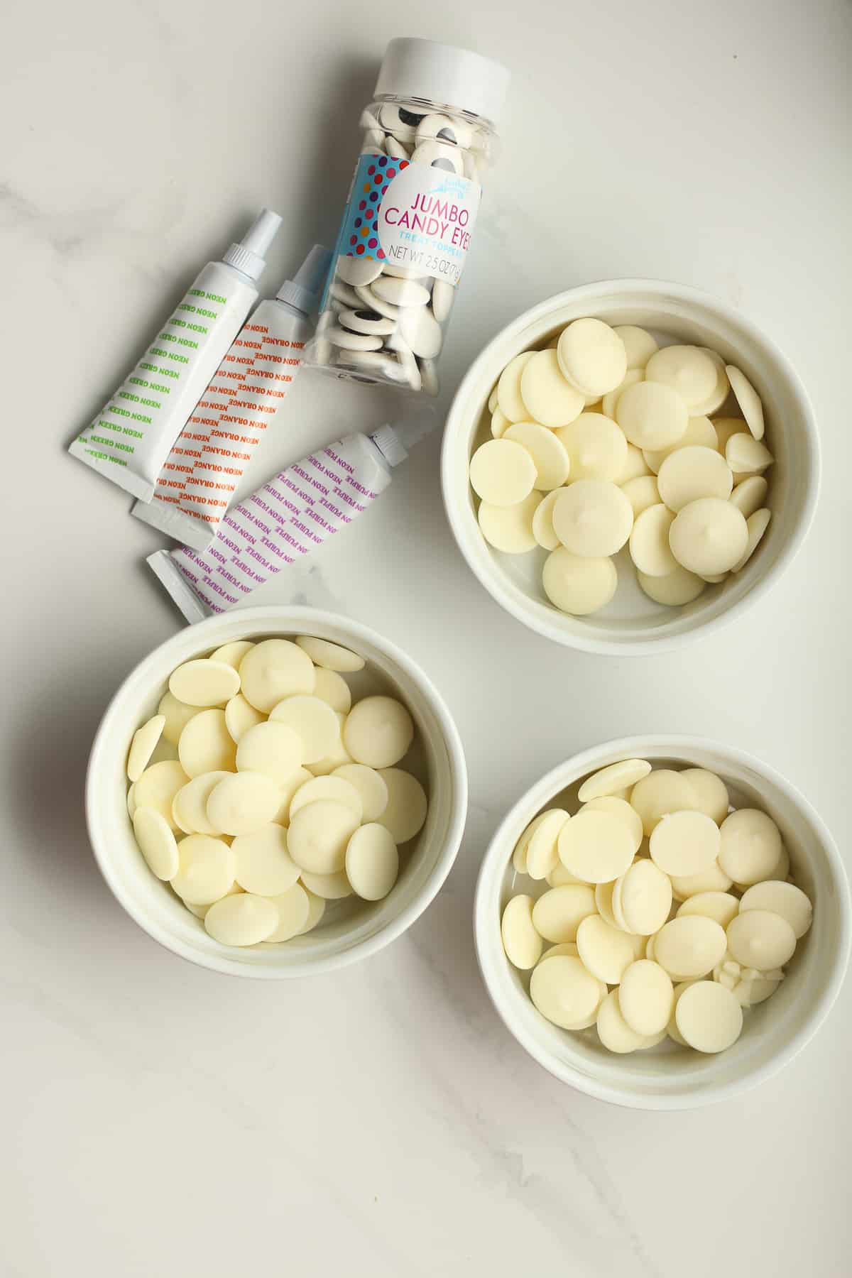 Three bowls with white melting wafers, and other decorating ingredients.