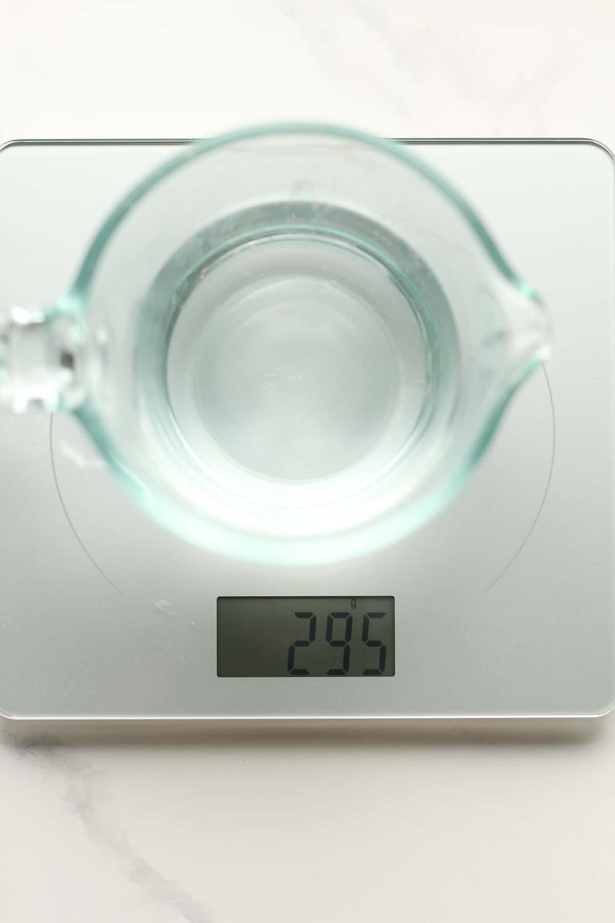 Filtered water in a measuring cup on a scale.