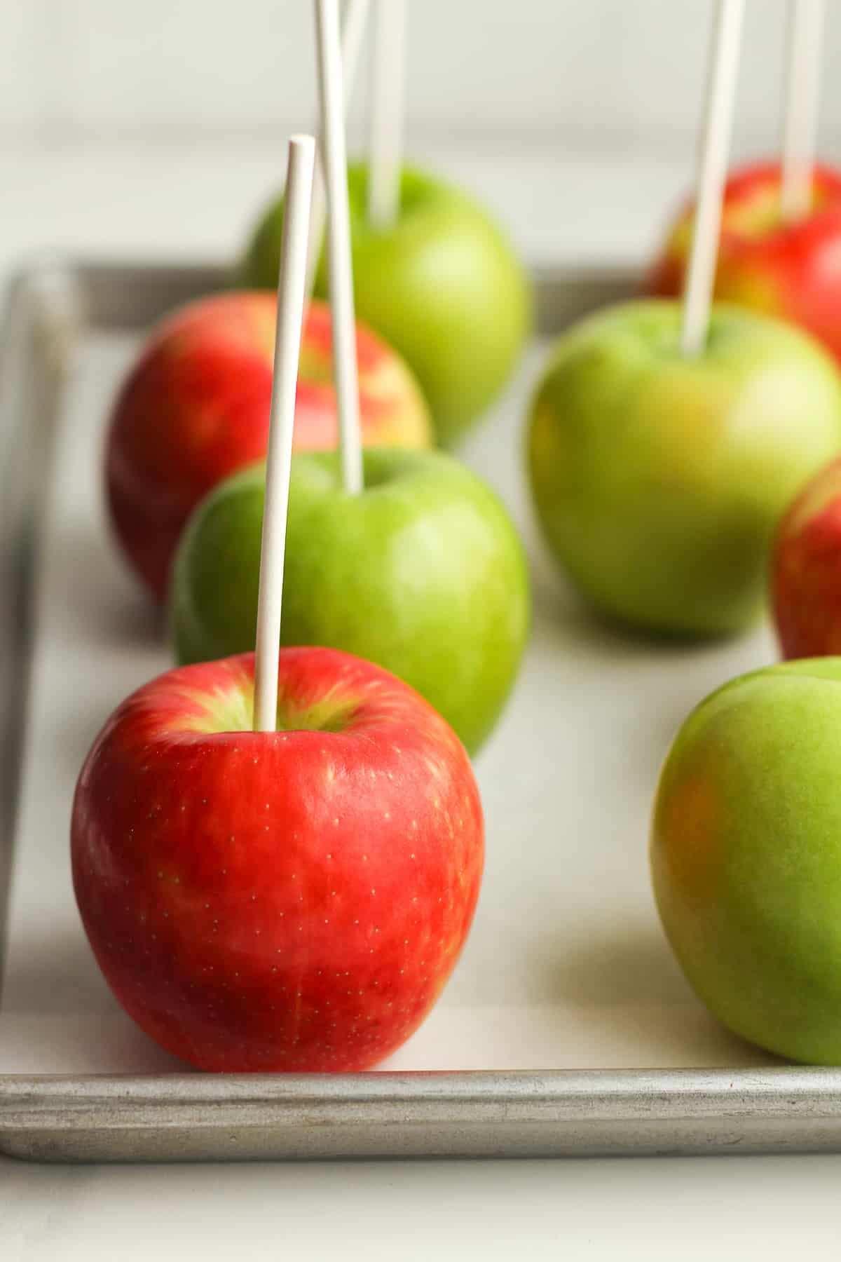 A tray of green and red apples on a pan.