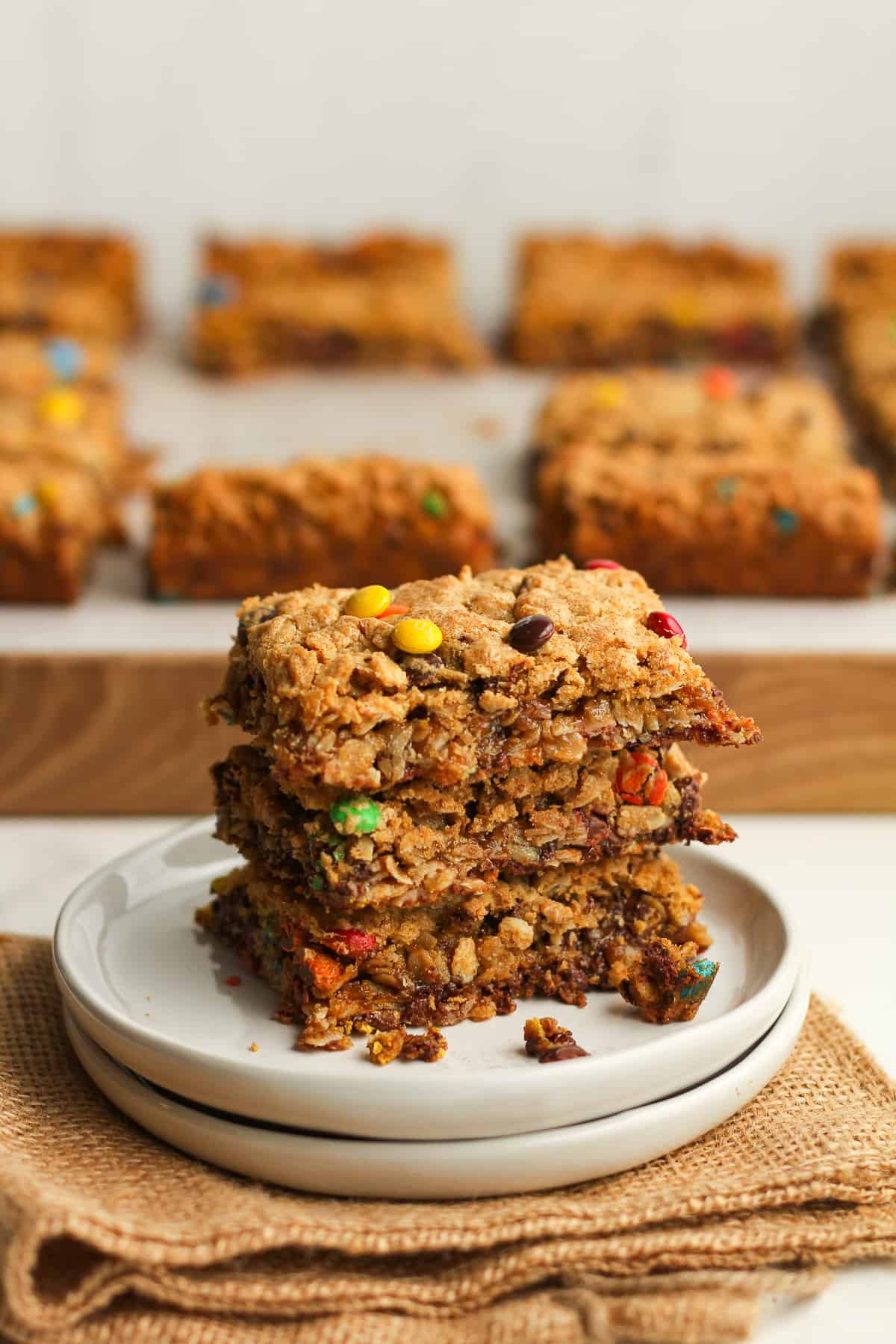 A stack of three monster cookie bars on a plate.