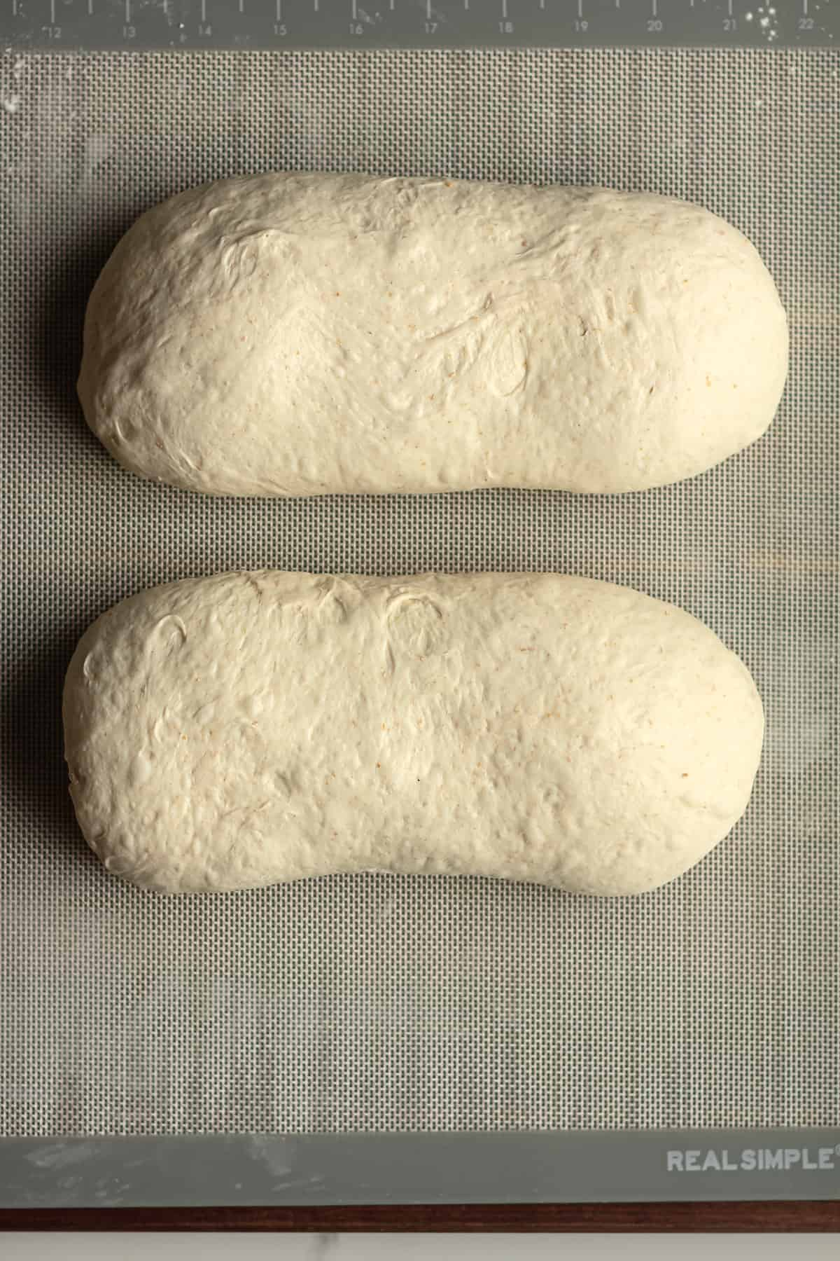 Two mounds of sourdough on a baking mat.