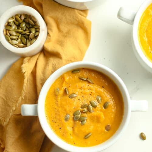Three bowls of squash soup.