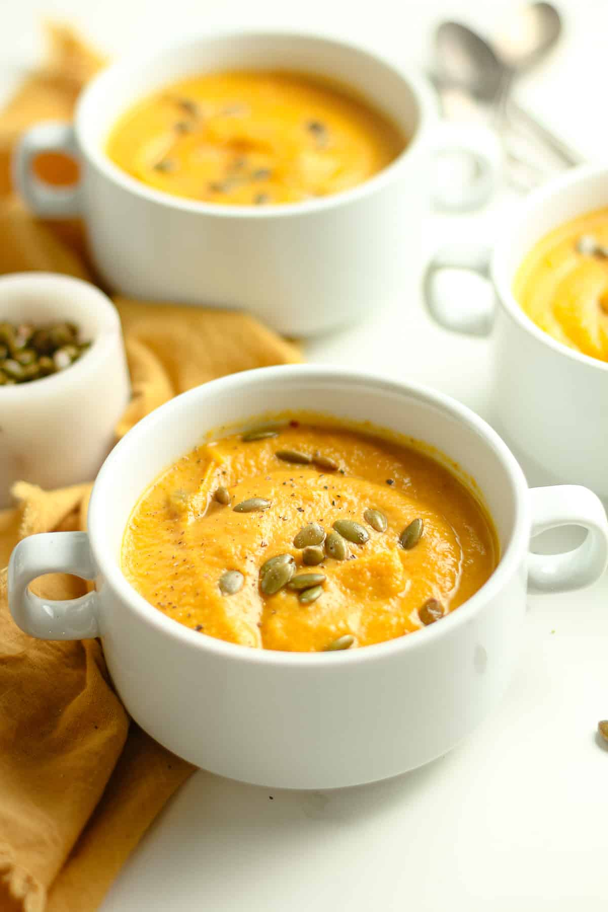 Side shot of three bowls of Autumn Squash soup.
