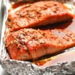 Side shot of two large pieces of salmon in foil.