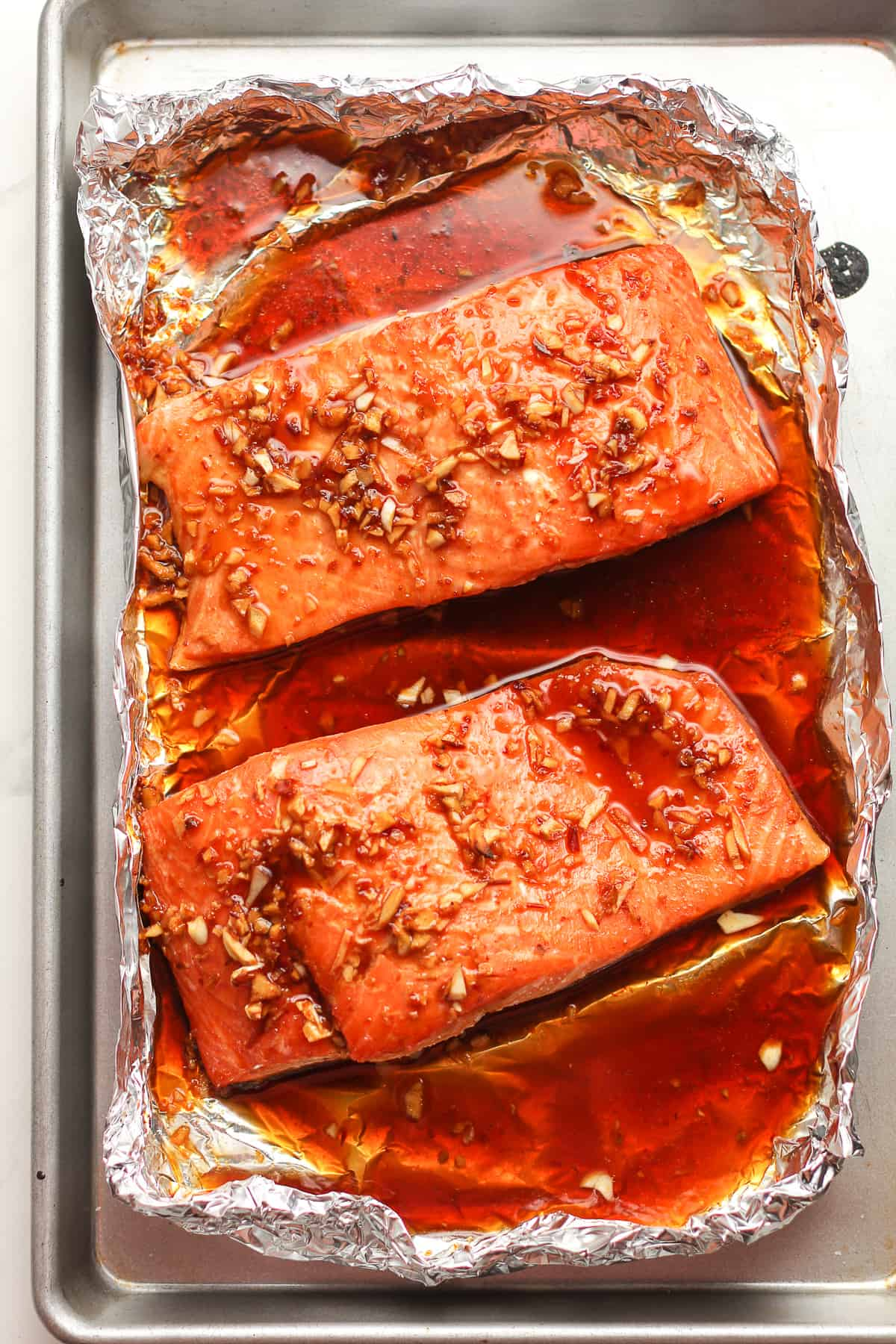 Overhead shot of two large pieces of baked salmon in foil.