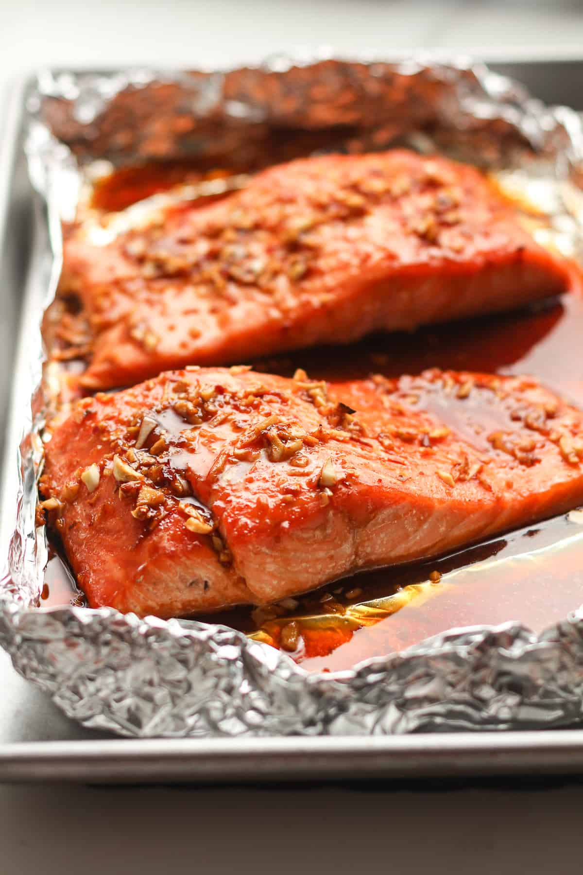 Side shot of two large pieces of baked salmon.