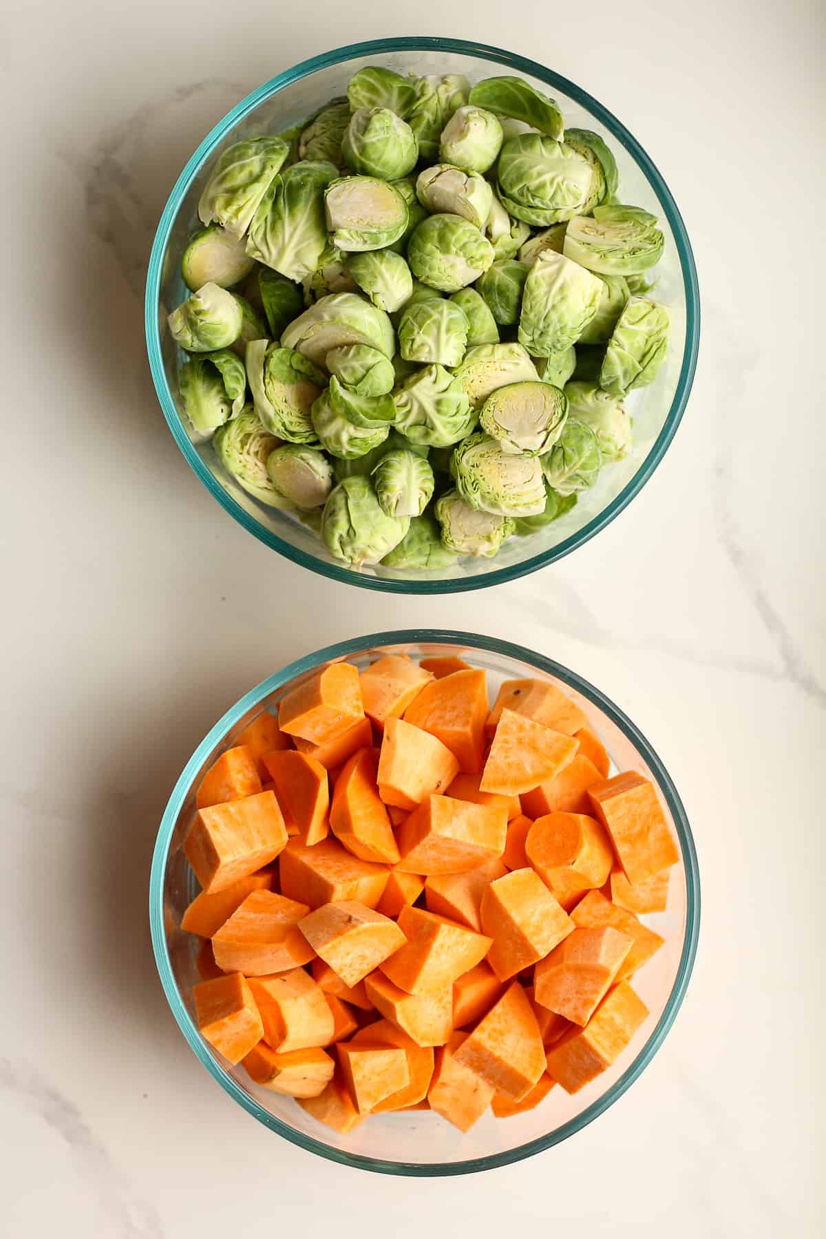 A bowl of chopped Brussels sprouts and another of chopped sweet potatoes.