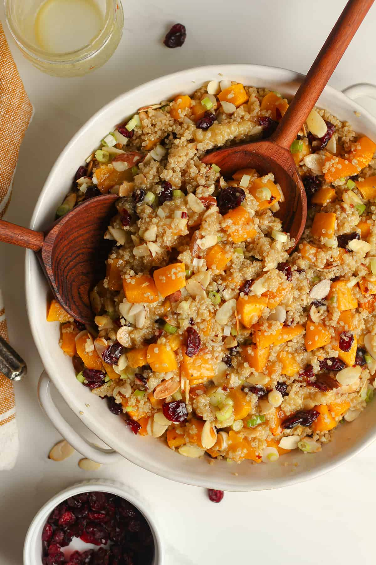 Overhead shot of a bowl of butternut squash quinoa salad with wooden spoons.