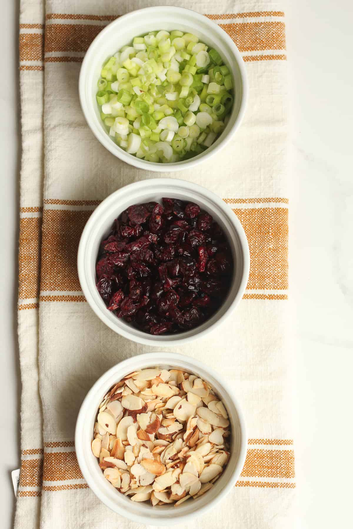 Three bowls of green onion, cranberries, and shaved almonds.