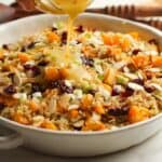Side shot of a bowl of butternut squash quinoa salad with dressing pouring over top.
