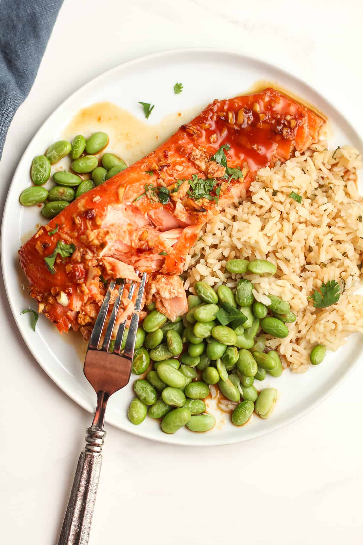 A plate of baked Asian salmon with a fork.