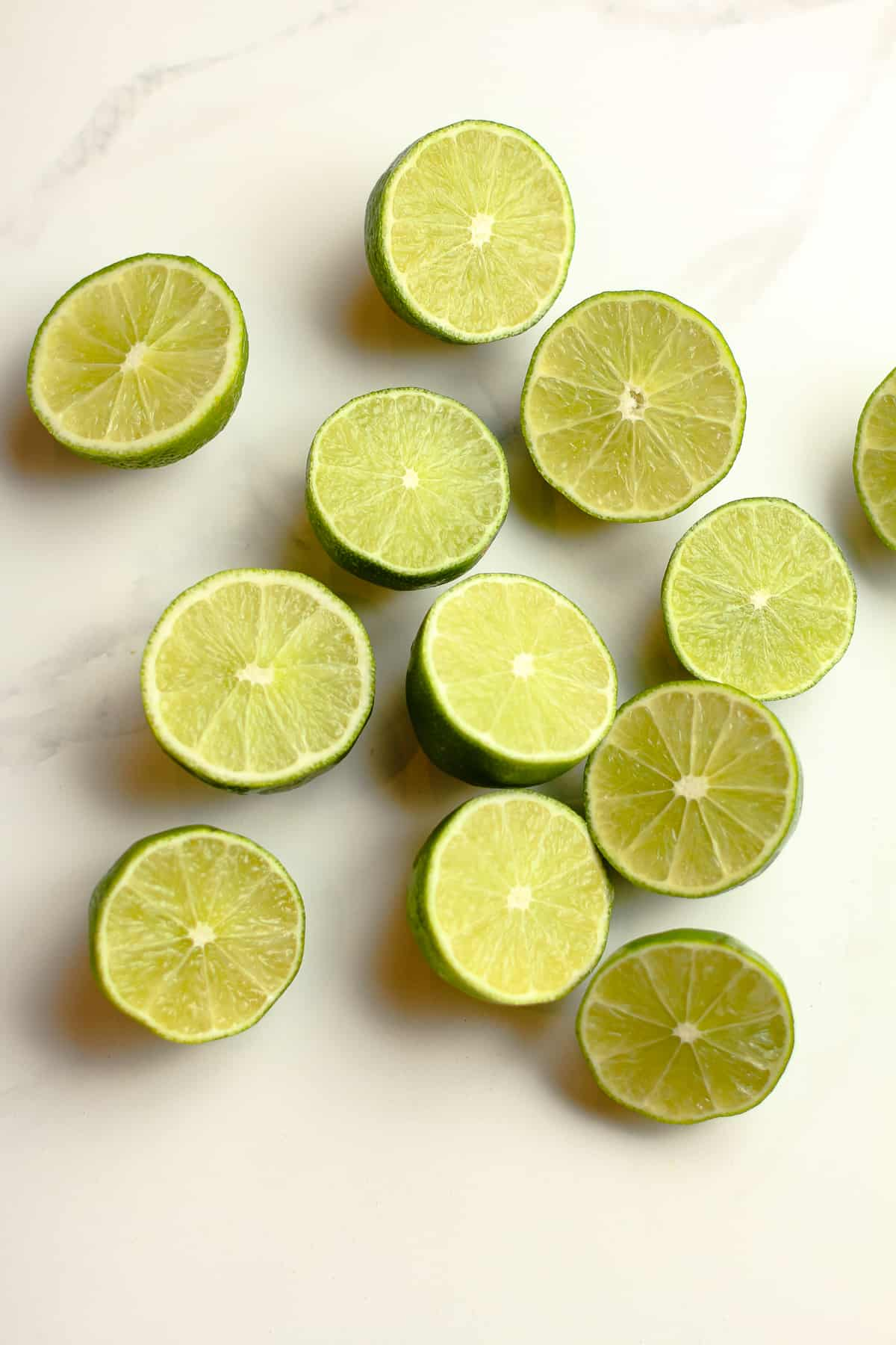 Halved limes on a white surface.