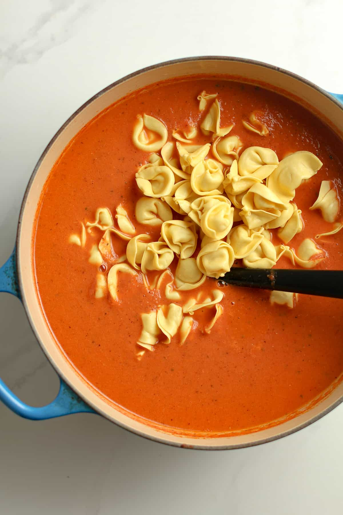 The pot of soup with the tortellini added in.