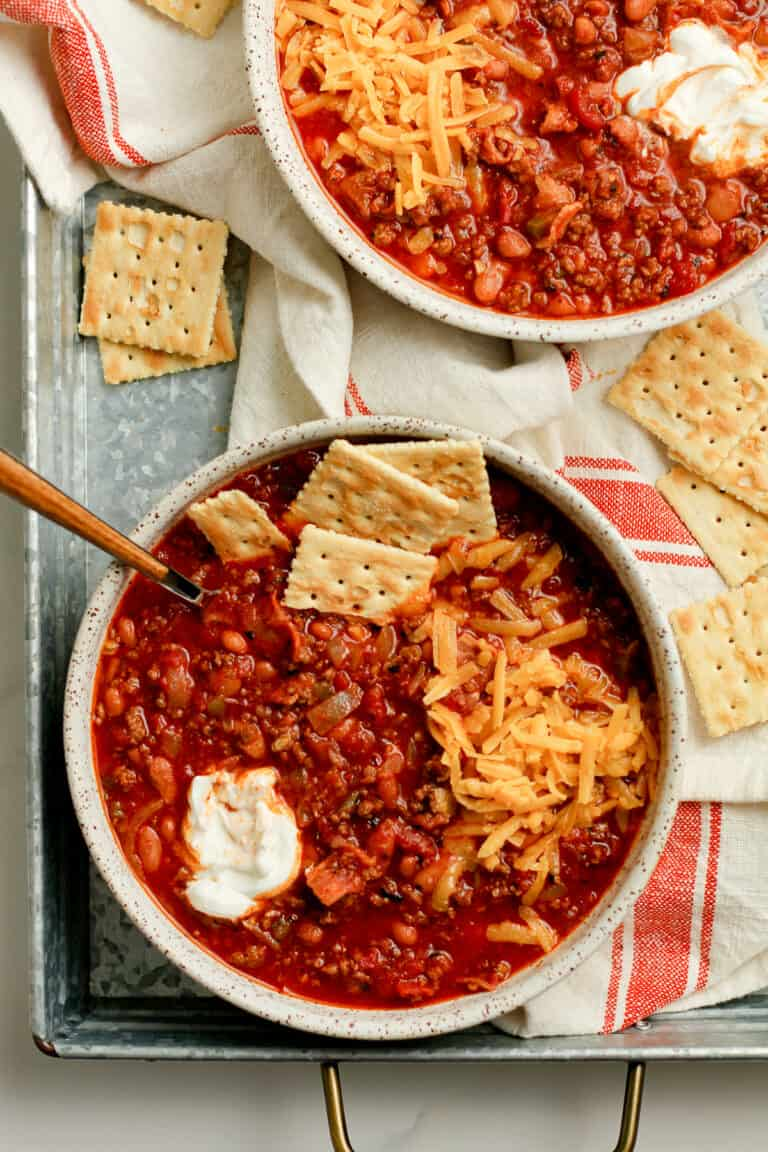 Two bowls of beef chilii with crackers.